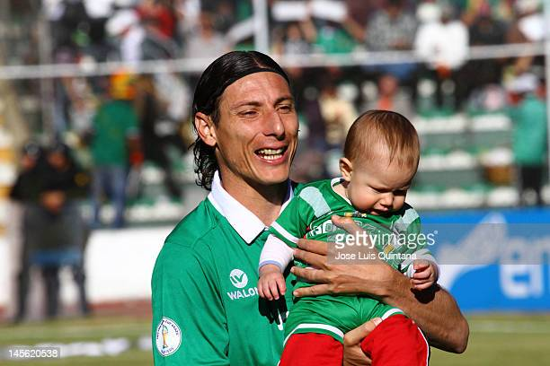 Bolivia midfielder Pablo Escobar with his child before a match between Chile and Bolivia at Hernando Siles Stadium as part of the fifth round of the...
