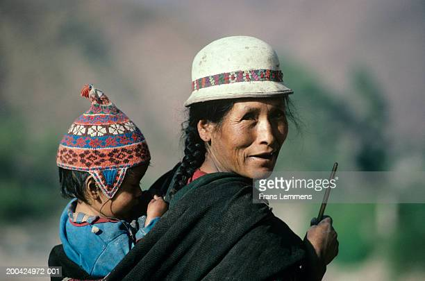 Bolivia, Potolo, woman spinning wool while carrying child on back