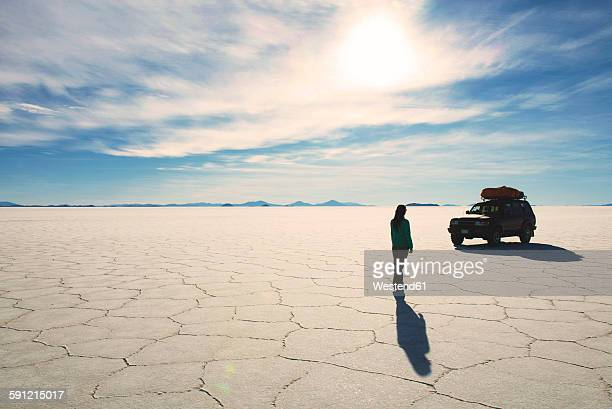 Bolivia, Potosi, Woman walking towards her 4x4 in Uyuni salt flats