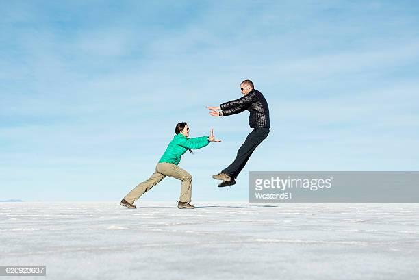 Bolivia, Salar de Uyuni, woman kicking man