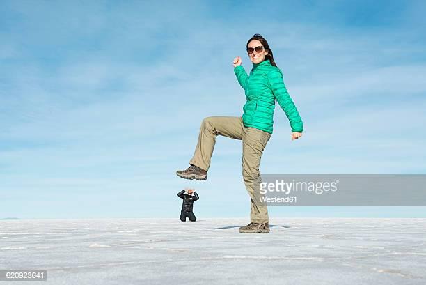 Bolivia, Salar de Uyuni, woman kicking small man, visual illusion