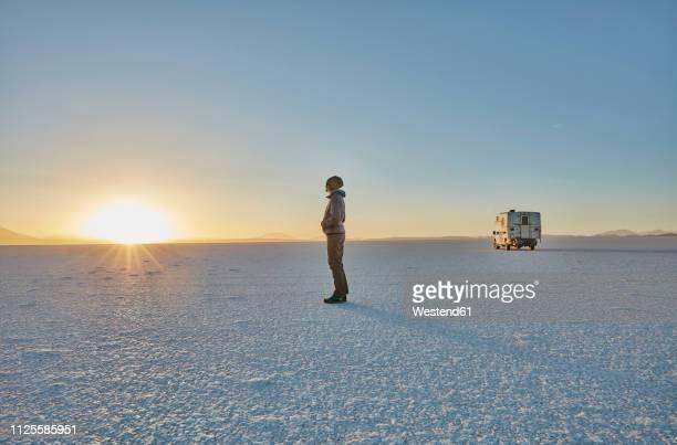 bolivia, salar de uyuni, woman standing at camper on salt lake at sunset - salt flat stock pictures, royalty-free photos & images