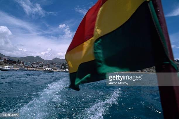 bolivia, south american flag flying with town of copacabana in background, bolivia, south america - bandera boliviana fotografías e imágenes de stock
