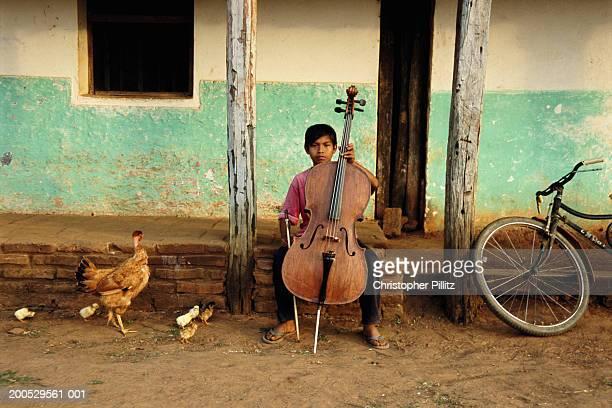 Bolivia, Urubicha, member of orchestra practising cello outside house