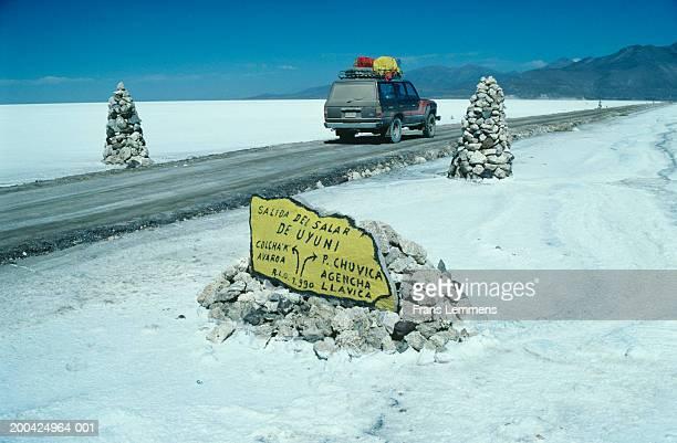 bolivia, uyuni salt lake, 4x4 passing road sign - road salt stock pictures, royalty-free photos & images