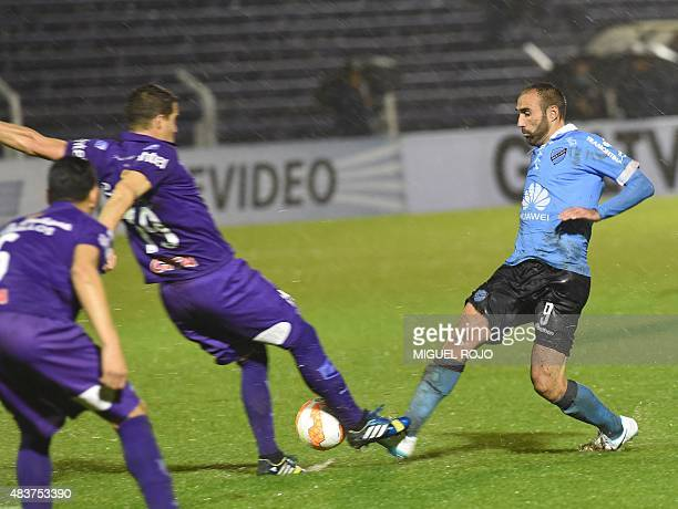 Bolivian Bolivar's Jose Sanchez vies for the ball with Andres Scotti of Uruguayan Defensor Sporting during their Sudamericana Cup football match at...