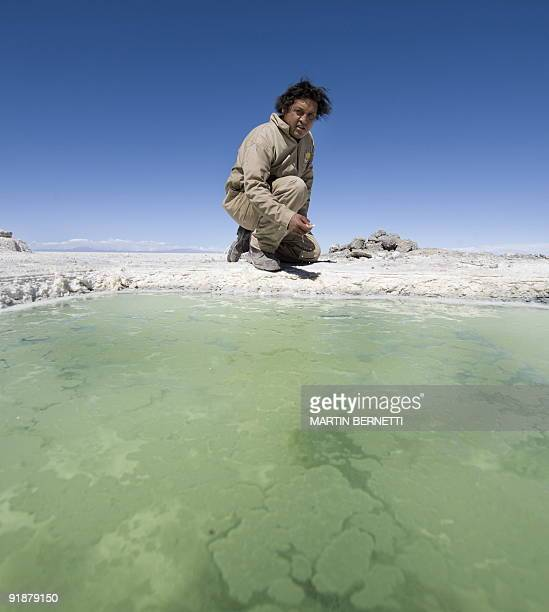 Bolivian engineer Marcelo Aguirre crouches beside a pool of brine at the Uyini Salt Flats in Bolivia October 10 2009 The Uyuni Salt flats has one of...