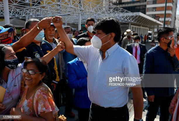 Bolivian ex-president Evo Morales, wearing a face mask, greets followers upon arrival to visit a polling station in downtown Caracas, on December 6...