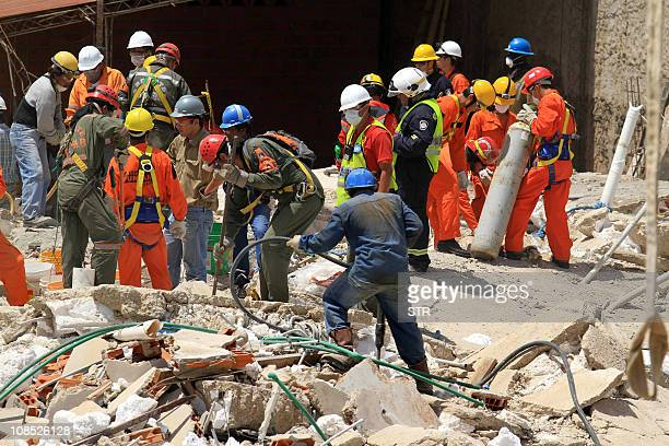 Bolivian firefighters and rescuers from Mexico Chile Peru Brazil Argentina and Venezuela search for survivors on January 29 2011 amid the ruins of a...