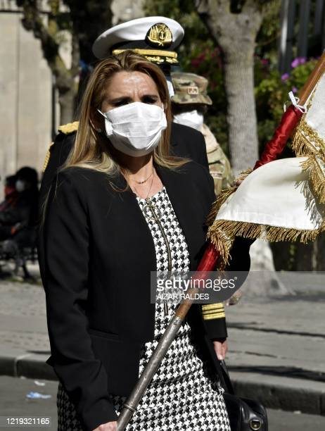 Bolivian interim President Jeanine Anez wears a face mask while attending a Corpus Christi procession at the Plaza de Armas in front of the...