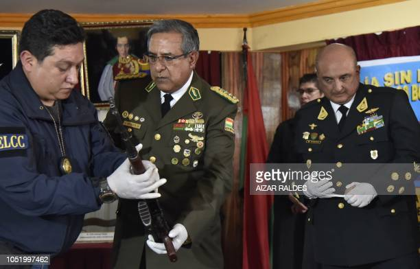 Bolivian police commander Alfonso Mendoza holds a rifle handed over to him by Peruvian National Police commander Richard Douglas Zubiate in the...
