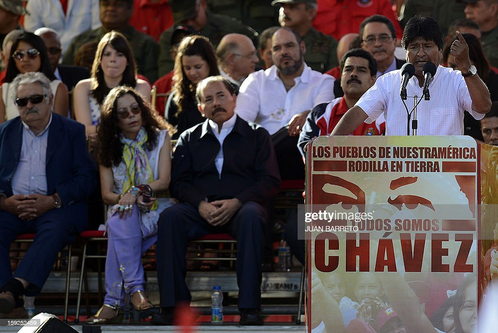 Bolivian President Evo Morales delivers a speech during a massive gathering in homage of Venezuelan President Hugo Chavez in front of Miraflores presidential palace in Caracas on January 10, 2013. With cancer-stricken President Hugo Chavez hospitalized in Cuba, thousands of flag-waving Venezuelans in red shirts filled the streets of Caracas Thursday to inaugurate his new term without him. Bands played anthems from street-side stages as people poured out of buses to make their way on foot toward the Miraflores presidential palace for a symbolic swearing-in of the people in place of Chavez, who is too sick to take the oath of office. AFP PHOTO/Juan BARRETO