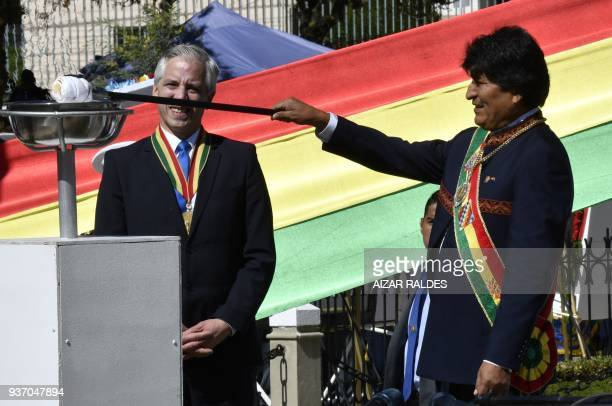 Bolivian President Evo Morales lights a votive flame as VicePresident Alvaro Garcia Linera looks on at the Eduardo Avaroa Monument in La Paz on March...