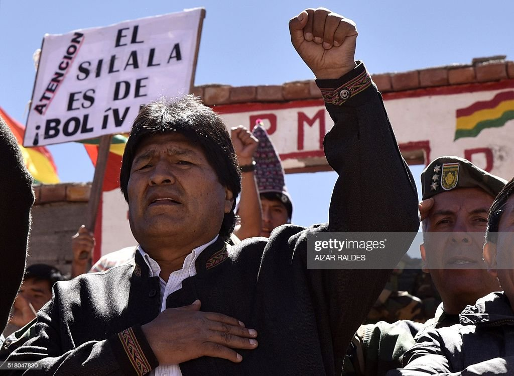 Bolivian President Evo Morales sings the national anthem next to a sign reading 'The Silala is Bolivian' during a visit to the Silala springs, in Potosi department, southwestern Bolivia, 4 km away from the border with Chile, on March 29, 2016. The Silala water system is the new dispute between Bolivia and Chile and the International Court of Justice (ICJ) of The Hague declared itself competent in the matter past September.