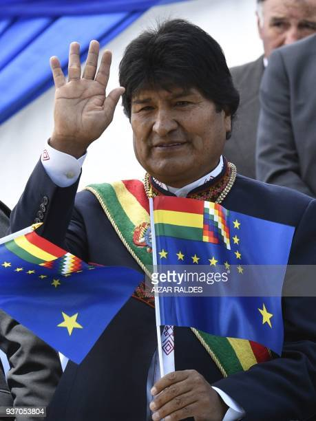 "Bolivian President Evo Morales waves as he holds a so-called ""flag of maritime revindication"" during the commemoration of the 139th anniversary of..."