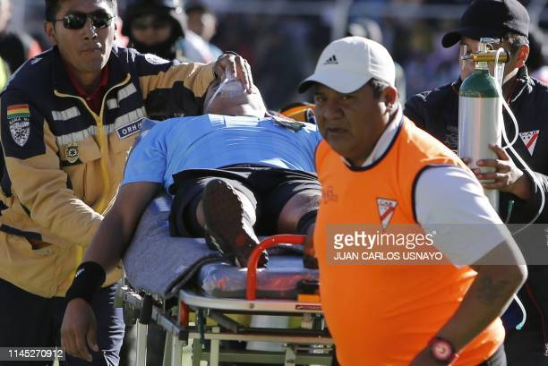 Bolivian referee Victor Hugo Hurtado is taken away on a stretcher during Bolivia's first division football match between Always Ready and Oriente...