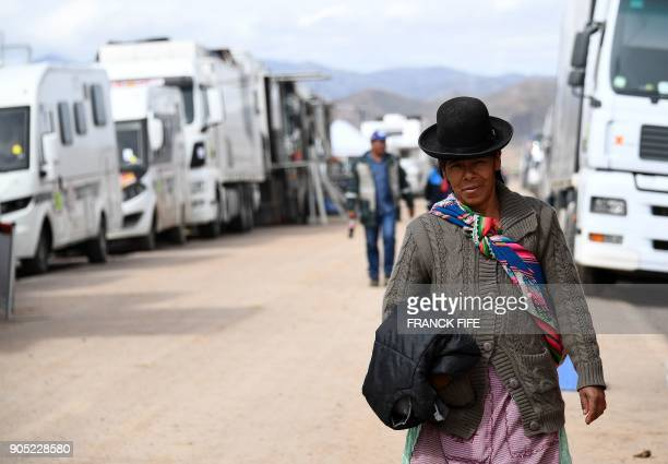 A Bolivian woman in traditional attire walks at the bivouac at the end of the Stage 8 of the 2018 Dakar Rally between Uyuni and Tupiza Bolivia on...