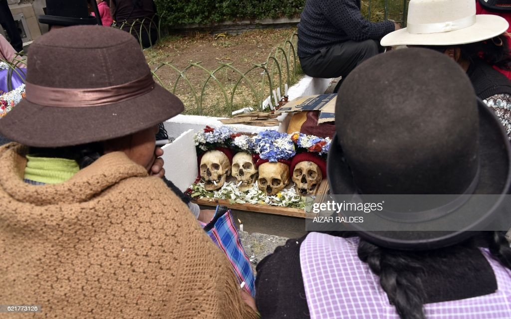 Bolivians perform rituals with their 'natitas' (snub-nosed) human skulls, at the Central Cemetery of La Paz, on November 8, 2016. The natitas are meant to protect their owners, who keep them at home all year long and bring them to the cemetery chapels every 8 of November to perform rituals which end up in a traditional party. /