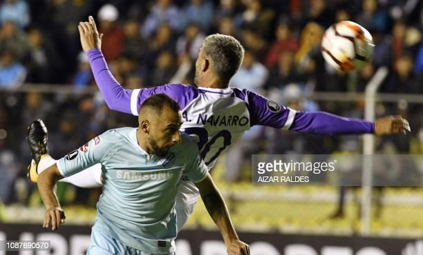 Bolivia's Bolivar player Marcos Riquelme vies for the ball with Alvaro Navarro of Uruguay's Defensor Sporting during their Copa Libertadores football...