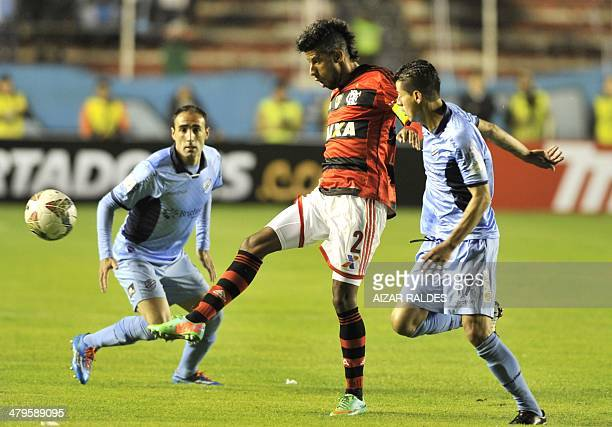 Bolivia's Bolivar players Jose Luis Sanchez and Juan Carlos Arce try to mark Leandro Moura of Brazil's Flamengo during their 2014 Copa Libertadores...
