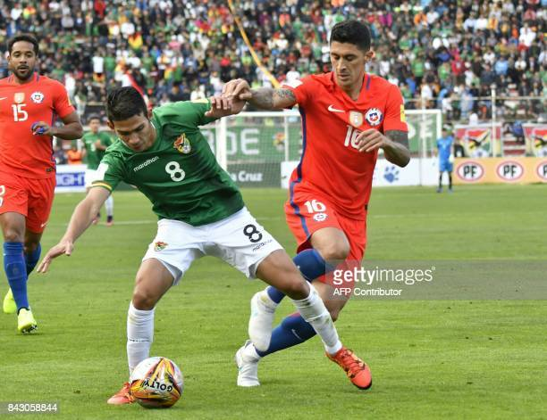 Bolivia's Diego Bejarano and Chile's Pedro Pablo Hernandez vie for the ball during their 2018 World Cup qualifier football match in La Paz on...