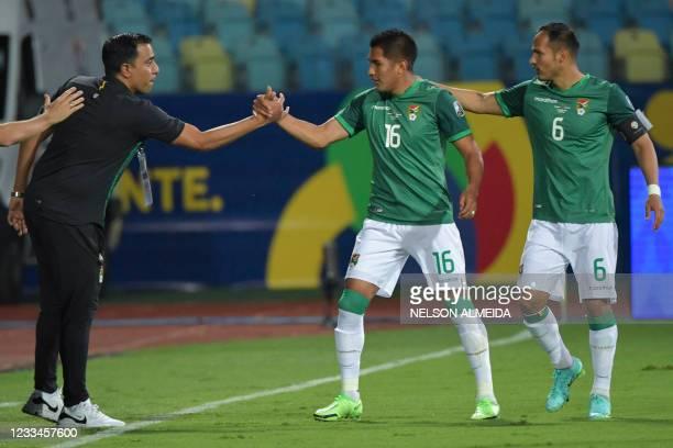 Bolivia's Erwin Saavedra celebrates with Bolivia's Venezuelan coach Cesar Farias after scoring against Paraguay during their Conmebol Copa America...