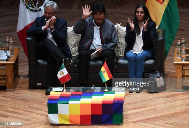 Bolivia's ex-President Evo Morales waves next to ex-Vice-President Alvaro Garcia Linera and the former president of the Bolivian Legislative Assembly...