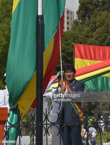 Bolivia's President Evo Morales Ayma raises Bolivia's national flag during the ceremony that marks the 138th anniversary of the Calama battle against...