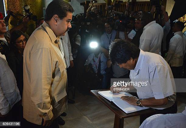 Bolivia's President Evo Morales signs the book of condolences as Venezuela's President Nicolas Maduro looks on after paying their last respects to...