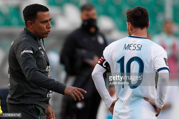 Bolivia's Venezuelan coach Cesar Farias talks to Argentina's Lionel Messi during their 2022 FIFA World Cup South American qualifier football match at...