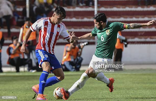 Bolivia's Walter Flores and Paraguay's midfielder Hernan Perez vie for the ball during their 2018 FIFA World Cup qualifier football match in La Paz...