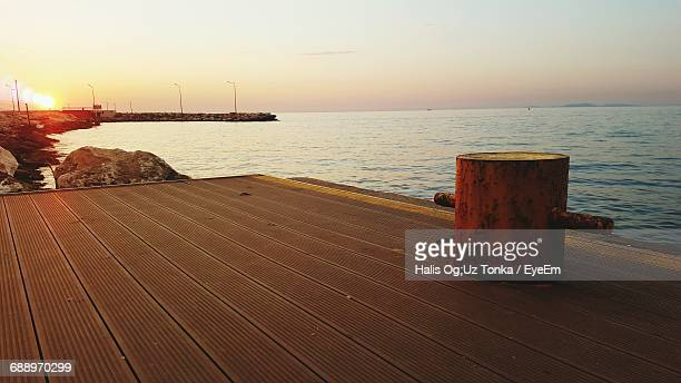 Bollard On Pier In Sea Against Sky During Sunset