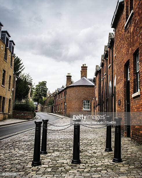 bollards on sidewalk by houses against sky - windsor castle stock pictures, royalty-free photos & images