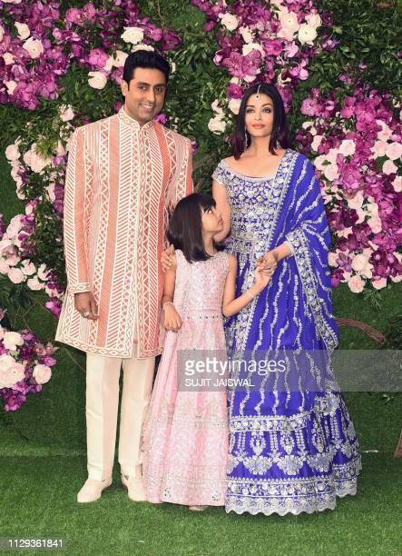 Bollywood actor Abhishek Bachchan poses for photographs along with his wife and actress and model Aishwarya Rai Bachchan and their daughter as they...