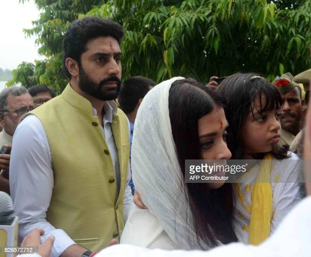 Bollywood actor Abhishek Bachchan walks along his wife actress Aishwarya Rai Bachchan and their daughter Aaradhya Bachchan after immersing ashes of...