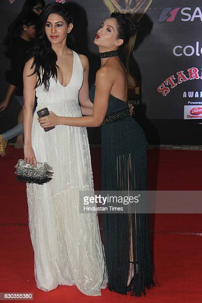 Bollywood actor Amyra Dastur and Nora Fatehi pose on red carpet for shutterbugs during the Sansui Colors Stardust Awards 2016 on December 19 2016 in...