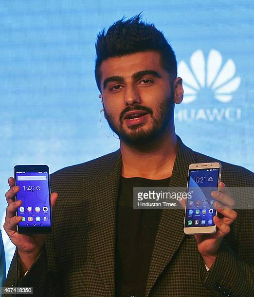 Bollywood actor Arjun Kapoor poses with Honor 6 Plus and Honor 4X Smartphones during the launch on March 24 2015 in New Delhi India Chinese handset...