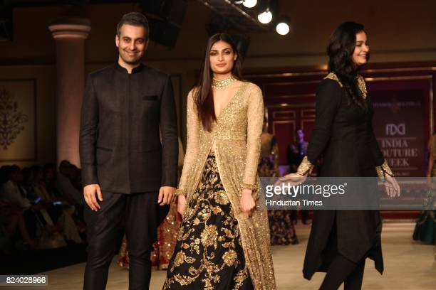 Bollywood actor Athiya Shetty walks on the ramp showcasing the collection of designer duo Shyamal Bhumika during the third day of India Couture Week...