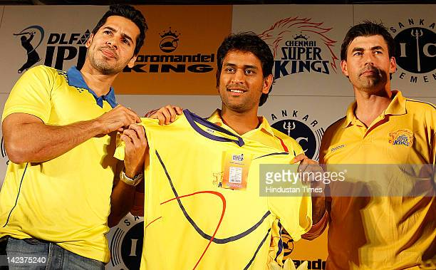 Bollywood actor Dino Morea Chennai Superking Captain MS Dhoni and Coach Stephen Fleming pose with a Tshirt during the launch of the new range of team...