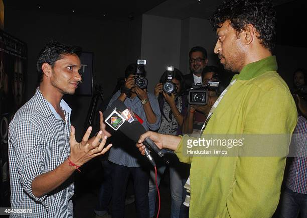 Bollywood actor Irrfan Khan holding media mikes to a fan during the screening of film Qissa at Light box, Santracruz on February 19, 2015 in Mumbai,...