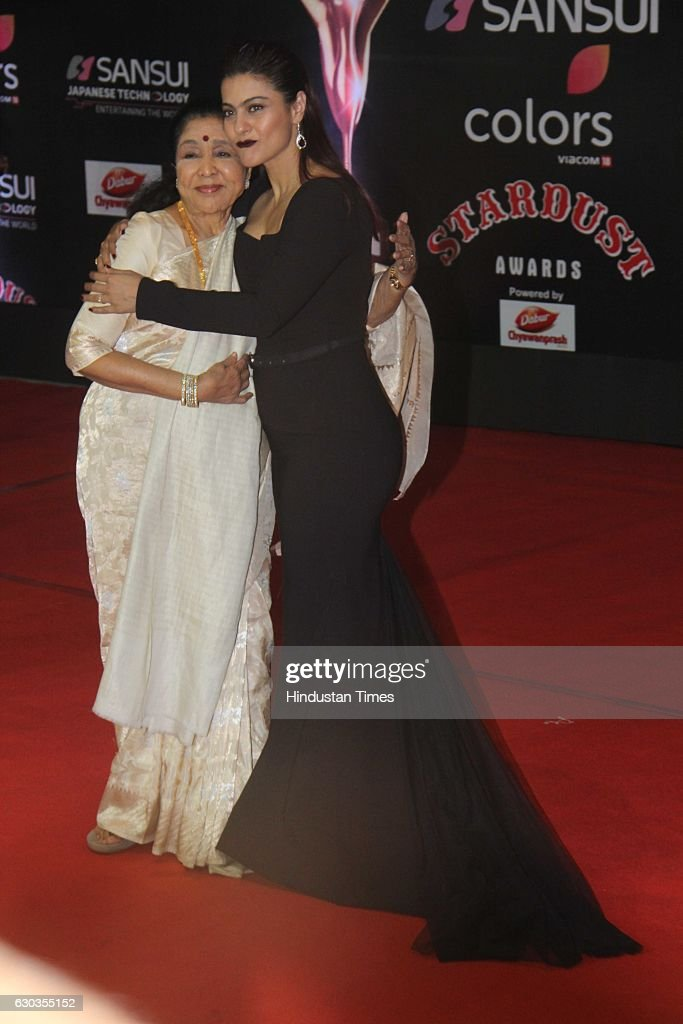 Bollywood actor Kajol Devgan along with veteran singer Asha Bhosle poses on red carpet for shutterbugs during the Sansui Colors Stardust Awards 2016..