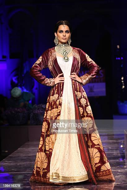 Bollywood actor Kangana Ranawat presents a creation by Indian designer JJ Valaya during the Grand Finale show at Wills Lifestyle India Fashion Week...