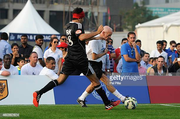 Bollywood actor Ranbir Kapoor tackles Mumbai City FC coach Peter Reid during an exhibition match played between BPL legends and All star FC from...