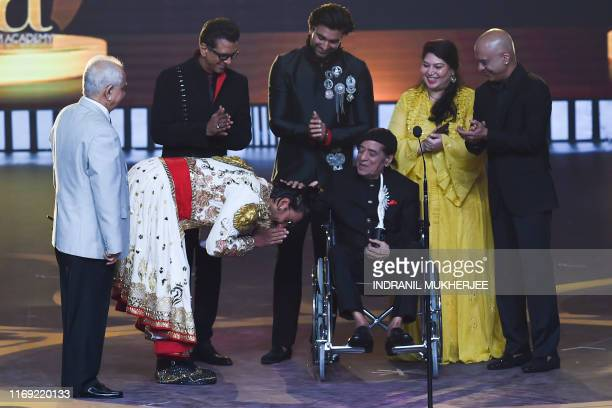 Bollywood actor Ranveer Singh bows after actor Jagdeep received the Lifetime Achievement award during the 20th International Indian Film Academy...