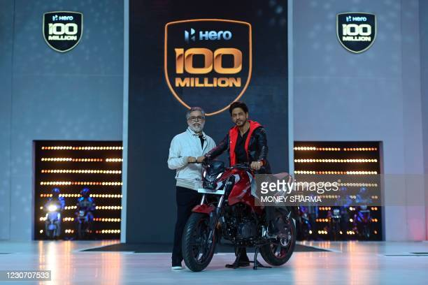 Bollywood actor Shah Rukh Khan and Pawan Munjal, Chairman and CEO of the Hero MotoCorp, pose for pictures during the unveiling of the companys 100...