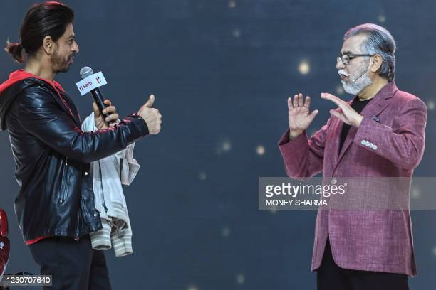 Bollywood actor Shah Rukh Khan and Pawan Munjal, Chairman and CEO of Hero MotoCorp , gesture during the unveiling of the company's 100 millionth...