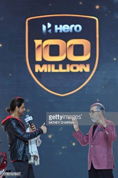 Bollywood actor Shah Rukh Khan and Pawan Munjal, Chairman and CEO of the Hero MotoCorp gesture during the unveiling of the companys 100 millionth...