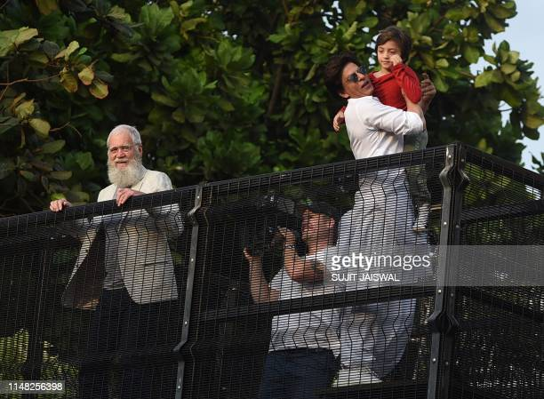 Bollywood actor Shah Rukh Khan holds his son as he prepares to greet his fans during Eid alfitr celebrations next to US television host David...