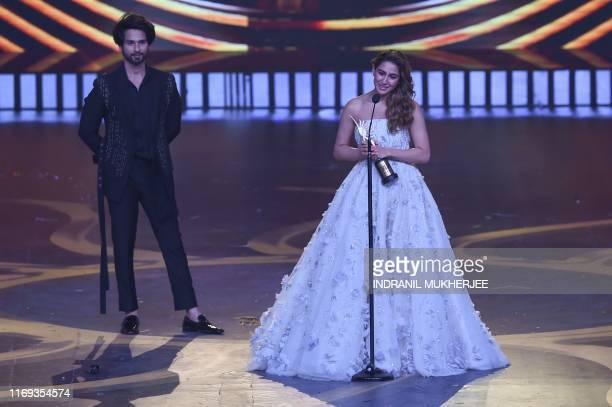 Bollywood actor Shahid Kapoor looks on as actress Sarah Ali Khan reacts after receiving the Best Debutant Female award during the 20th International...