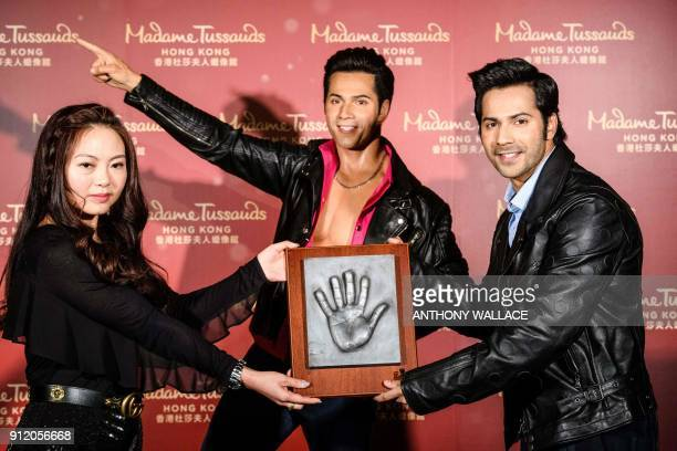 Bollywood actor Varun Dhawan and Madame Tussauds general manager Jenny You pose with a cast of Dhawan's hand in front of his newly unveiled wax...
